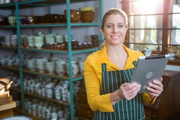 Portrait of female potter using digital tablet