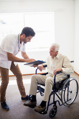 Nurse showing senior man a document