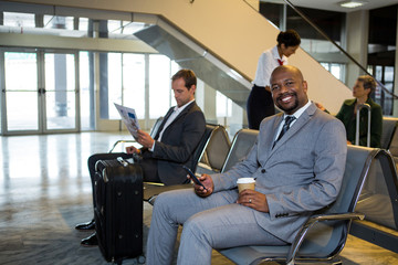 Businessman using mobile phone in waiting area at airport terminal