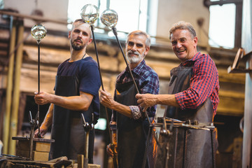 Portrait of team of glassblowers shaping a glass on the blowpipe