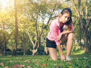 Asian young woman on mark to set ready for jogging exercise to buld up her body on glass in warm light morning. Young woman do exercise workout in park to make body beauty. Outdoor jogging in the park