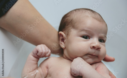 Closeup of newborn girl in the bathtub held by her mother\