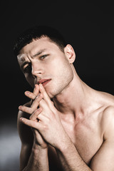 Portrait of pensive bare-chested man holding heads near chin. Reverie concept