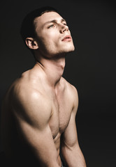 Side view contemplative young man with attractive body watching directly