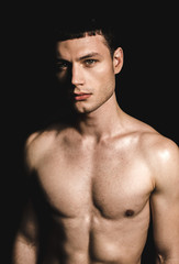 Portrait of confident male stripped to waist. He isolated on black background. Assurance concept