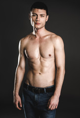 Portrait of serene young bare-chested man isolated on dark background. Calm guy with attractive body concept