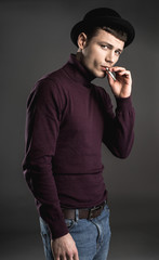 Portrait of relieved male smoking cigarette. He isolated on dark background. Tranquility concept