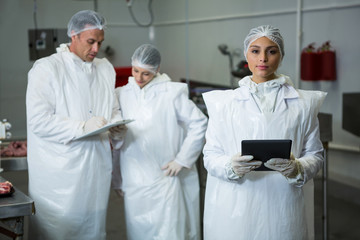 Technician holding digital tablet at meat factory