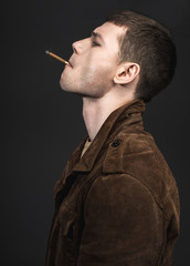 Side view pensive male piping cigarette. He wearing in modern jacket. He isolated on black background. Tough guy concept