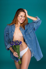 Portrait of sexy naked girl posing with bouquet of flowers. She is looking at camera and smiling while wearing only jacket and panties. Isolated