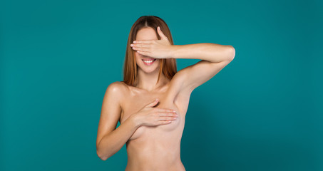 You cannot see me. Cheerful young woman is covering her nude breast by arm while closing eyes by hand. She is standing and smiling. Isolated