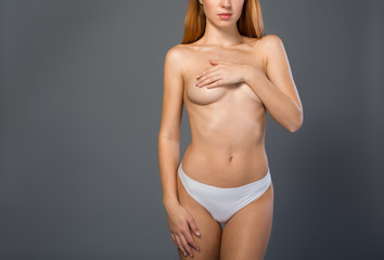 Sensual young woman standing and closing her breast by arm. She is wearing only white panties. Isolated and copy space