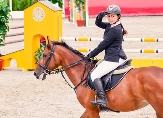 Beautiful girl in uniform and bay dressage horse at showjumping competition. Equestrian sport background.