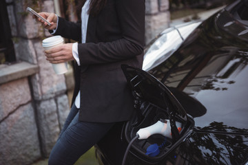 Woman using mobile phone while charging electric car