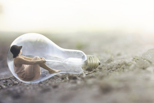 surreal moment of a small woman resting inside a light bulb