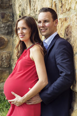 Pregnant woman with husband standing on wall vertical