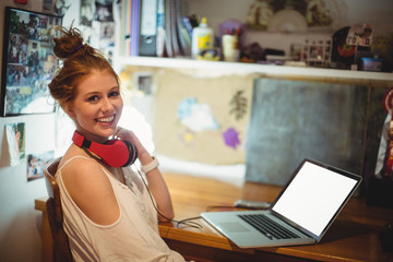 Portrait of woman sitting with laptop and headset