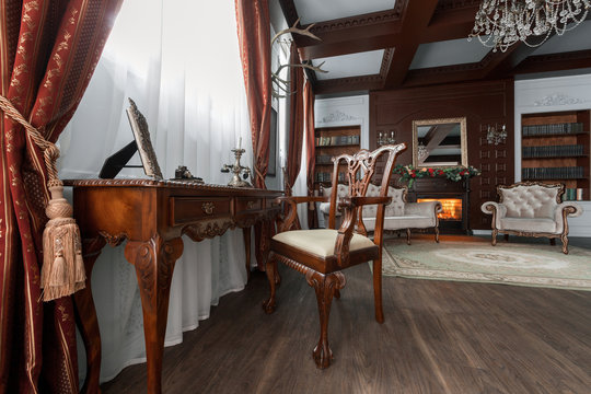 Old studying room with fabric armchairs and wooden table. Classic bookcase filled with books. Fireplace