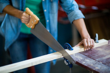Female carpenter cutting plank with hand saw