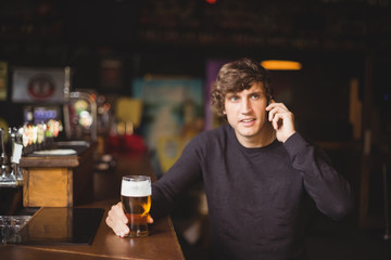 Man talking on mobile phone in bar