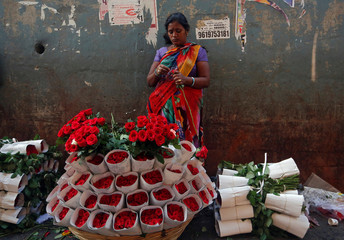 A vendor prepares a bouquet as she waits for customers at a market in Mumbai