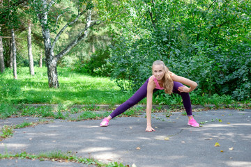 Female runner with beautiful figure doing stretching exercise