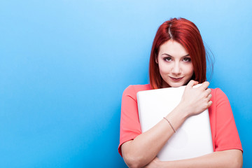 Beautiful redhead woman student holding a laptop in her arms on blue background