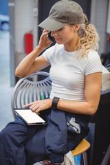 Female mechanic using digital tablet while talking on mobile phone