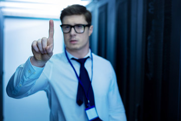 I love working. Good-looking inspired man working in a data center and pointing with his finger