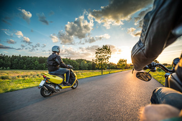 Motor biker riding on empty road with sunset light, concept of speed and touring in nature.