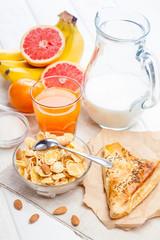 healthy breakfast. bowl of cornflakes, fruit, fresh juice, milk