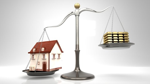 High price, expensive house mortgages and big credits symbolized by a house on a scale against stack of gold bars.