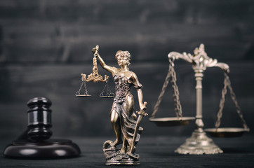 Lady Justice, Scales of Justice and Judge Gavel on a black wooden background.