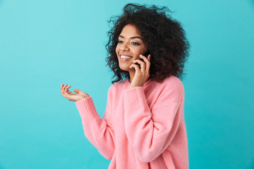 American happy woman in pink shirt smiling and speaking on black mobile phone, isolated over blue background