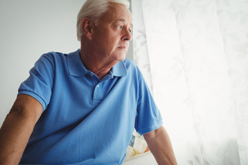 Thoughtful senior man sitting on his bed