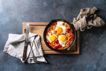 Traditional Israeli Cuisine dishes Shakshuka. Fried egg with vegetables tomatoes and paprika in cast-iron pan on wooden board with cloth and cutlery over blue texture background. Top view, space.