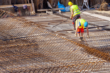 Construction workers prepare reinforcement for the foundations of the building. Concrete reinforcement.