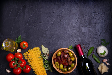 Selection of healthy food. Italian food background with spaghetti, cheese, olives, tomatoes, basil and wine. Slate banner background. View from above, top, flat lay with room for text