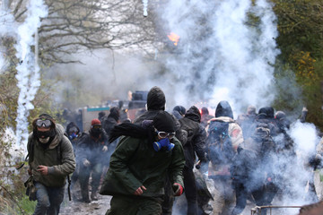 Tear gas floats in the air as protesters retreat and French gendarmes advance with an armoured vehicle during an evacuation operation in the zoned ZAD (Deferred Development Zone) in Notre-Dame-des-Landes