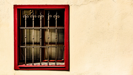 Window with red frame and metal grid