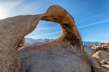 Mobius Arch on sunset with Whitney mountain on background. Alabama Hills, Eastern Sierra Nevada Mountains, Lone Pine, California, USA.