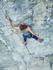 woman rock climber climbs on the cliff