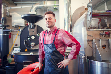 Photo of happy man in apron on background of industrial coffee grinder