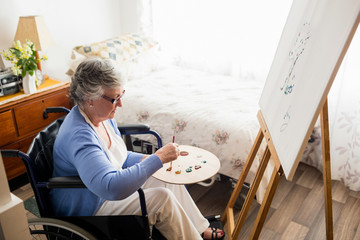 Senior handicapped woman painting while sitting at home