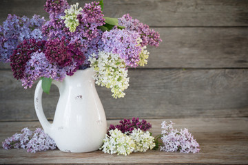 Foto auf Leinwand Flieder lilac in jug on old wooden background