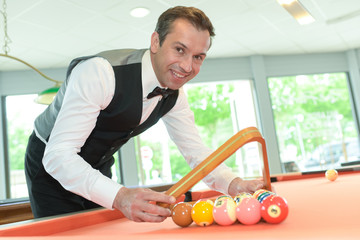 handsome man with suit sitting in billiard pool in club
