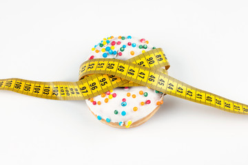 A beautiful donut covered with multicolored glaze covered with a centimeter tape. Healthy diet. Diet