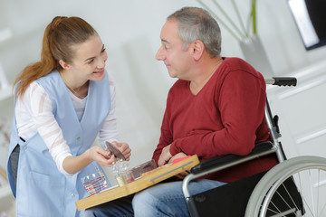 photo of happy elderly man with disability and helpful nurse