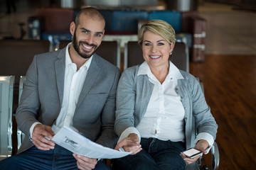 Portrait of smiling businesspeople sitting in waiting area with newspaper