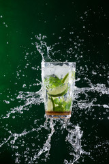 fresh mojito drink with liquid splash and crushed ice in freeze motion.